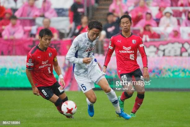 Ryo Shinzato of Ventforet Kofu controls the ball under pressure of Yoichiro Kakitani and Hiroshi Kiyotake of Cerezo Osaka during the JLeague J1 match...