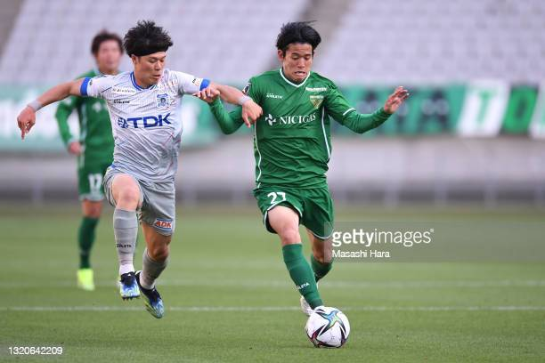 Ryoga Sato of Tokyo Verdy and Yuji Wakasa of Blaublitz Akita compete for the ball during the J.League Meiji Yasuda J2 match between Tokyo Verdy and...