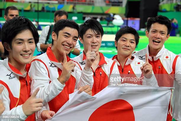 Ryohei Kato Kenzo Shirai Kohei Uchimura Koji Yamamuro and Yusuke Tanaka of Japan celebrate winning the gold medal after competing in the men's team...