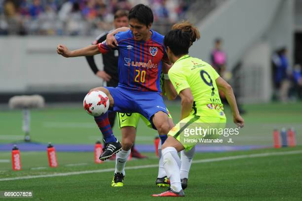 Ryoichi Maeda of FC Tokyo controls the ball under pressure of Daisuke Kikuchi and Yuki Muto of Urawa Red Diamonds during the J.League J1 match...