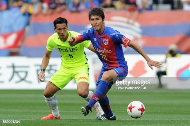 Ryoichi Maeda of FC Tokyo controls the ball under pressure of Tomoaki Makino of Urawa Red Diamonds during the J.League J1 match between FC Tokyo and...