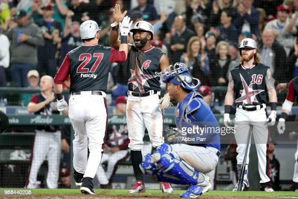 Ryon Healy high fives Denard Span of the Seattle Mariners after hitting a two run home run in the second inning against the Kansas City Royals during...
