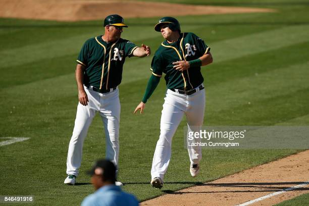 Ryon Healy of the Oakland Athletics dodges a pat on the back from third base coach Steve Scarsone on his way to home plate to score on a Matt Olson...
