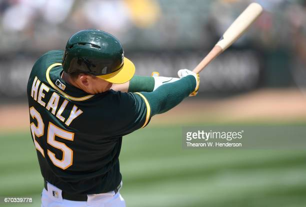 Ryon Healy of the Oakland Athletics hits an RBI single scoring Rajai Davis against the Texas Rangers in the bottom of the first inning at Oakland...
