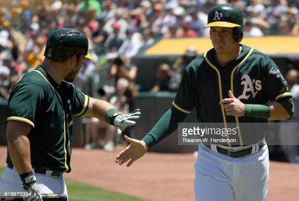 Ryon Healy of the Oakland Athletics is congratulated by Josh Phegley after Healy scored against the Cleveland Indians in the bottom of the first...