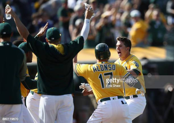 Ryon Healy of the Oakland Athletics is congratulated by teammates after he hit a walk-off home run in the ninth inning against the Detroit Tigers at...