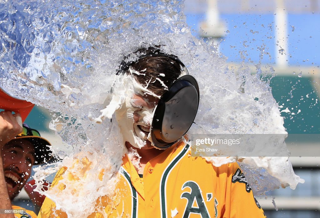 Ryon Healy #25 of the Oakland Athletics is covered in water by Adam Rosales #16 after he hit a walk-off home run in the ninth inning against the Detroit Tigers at Oakland Alameda Coliseum on May 7, 2017 in Oakland, California.