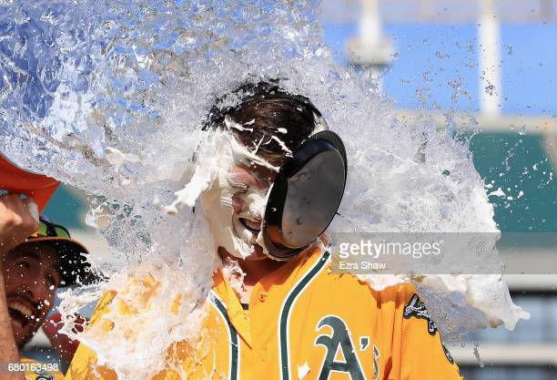 Ryon Healy of the Oakland Athletics is covered in water by Adam Rosales after he hit a walkoff home run in the ninth inning against the Detroit...
