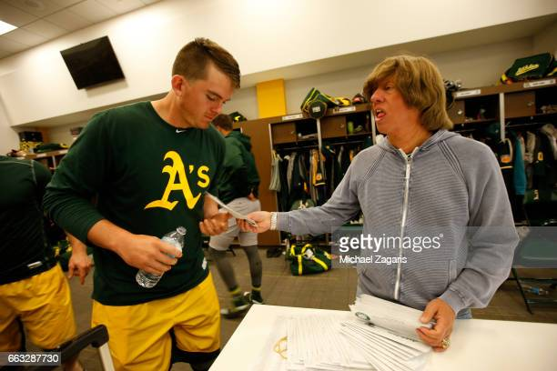 Ryon Healy of the Oakland Athletics receives his per diem from Director of Team Travel Mickey Morabito in the clubhouse prior to leaving for the game...