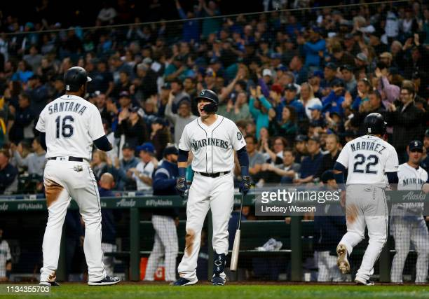 Ryon Healy of the Seattle Mariners center yells as he greets Domingo Santana after Santana and Omar Narvaez right scored on a double by Tim Beckham...