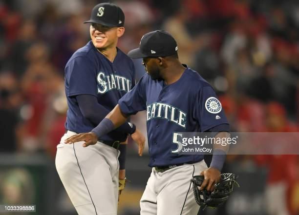 Ryon Healy of the Seattle Mariners gets a congratulatory pat from Guillermo Heredia after a 5-0 win over the Los Angeles Angels of Anaheim at Angel...