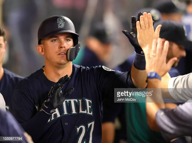 Ryon Healy of the Seattle Mariners is congratulated after being driven in by Kristopher Negron in the sixth inning against the Los Angeles Angels of...