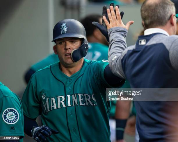 Ryon Healy of the Seattle Mariners is congratulated after scoring a run on a fielder's choice hit by David Freitas of the Seattle Mariners off of...