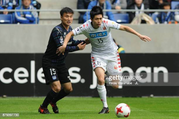 Ryosuke Shindo of Consadole Sapporo and Yasuyuki Konno of Gamba Osaka compete for the ball during the JLeague J1 match between Gamba Osaka and...