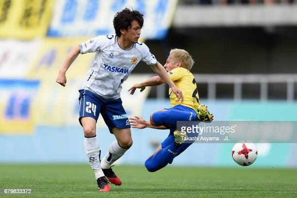 Ryosuke Tada of Tochigi SC is challenged by Tatsuya Onodera of Giravanz Kitakyushu during the JLeague J3 match between Tochigi SC and Giravanz...