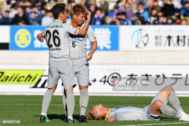 Ryosuke Tada Tatsuki Kohatsu and Kohei Hattori of Tochigi SC celebrate their 11 draw and the promotion to the J2 at the final whistle of the JLeague...