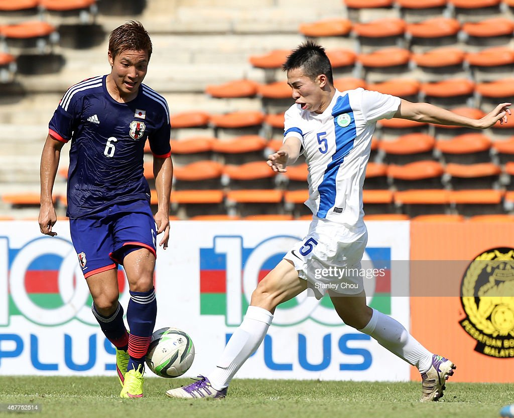 Ryosuke Yamanaka of Japan challenges G.I. Chan of Macau during the AFC U23 Championship Qualifier Group I match between Japan and Macau at Shah Alam Stadium on March 27, 2015 in Shah Alam, Malaysia.