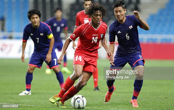 Ryosuke Yamanaka of Japan competes for the ball with Alkhebeezi Yousif of Kuwait during the Men's football Group D match between Japan and Kuwait at...