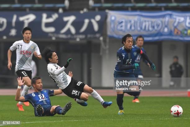 Ryota Kajikawa of Tokyo Verdy is challenged by Riki Matsuda of Avispa Fukuoka during the JLeague J1 Promotion PlayOff semi final match between Avispa...