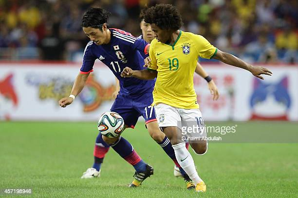 Ryota Morioka of Japan and William Borges Da Silva of Brazil challenge for the ball during the international friendly match between Japan and Brazil...