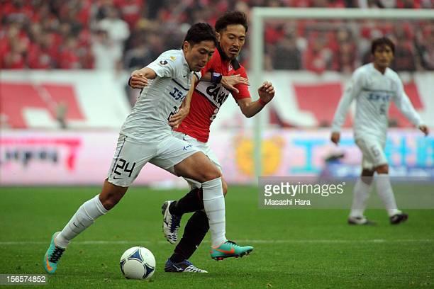 Ryota Moriwaki of Sanfrecce Hiroshima and Yuki Abe of Urawa Red Diamonds compete for the ball during the JLeague match between Urawa Red Diamonds and...