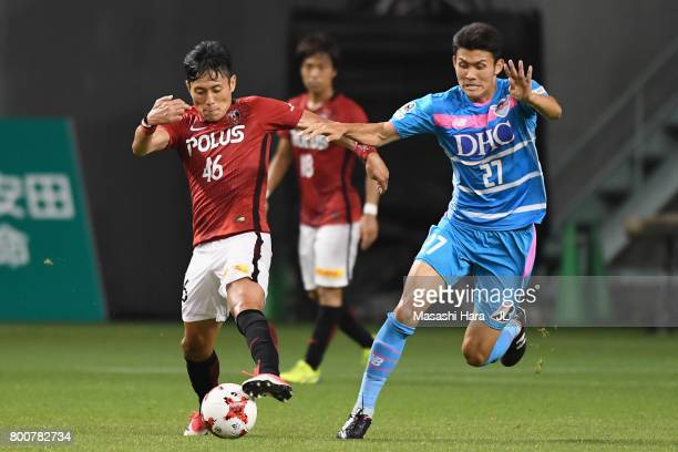 Ryota Moriwaki of Urawa Red Diamonds and Kyosuke Tagawa of Sagan Tosu compete for the ball during the JLeague J1 match between Sagan Tosu and Urawa...