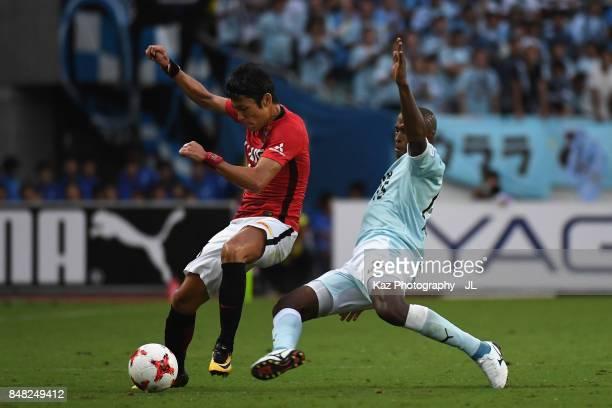 Ryota Moriwaki of Urawa Red Diamonds is tackled by Adailton of Jubilo Iwata during the JLeague J1 match between Jubilo Iwata and Urawa Red Diamonds...