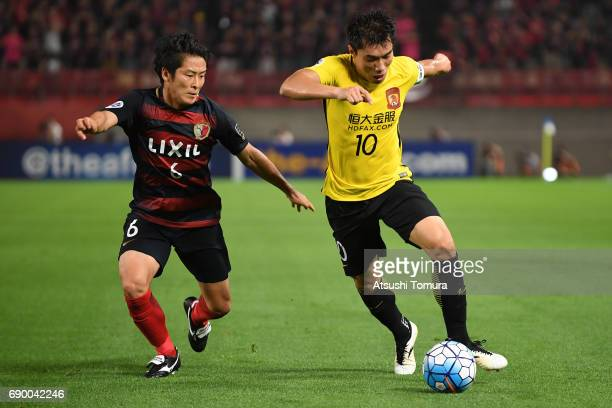 Ryota Nagaki of Kashima Antlers and Zhi Zheng of Guangzhou Evergrande compete for the ball during the AFC Champions League Round of 16 match between...