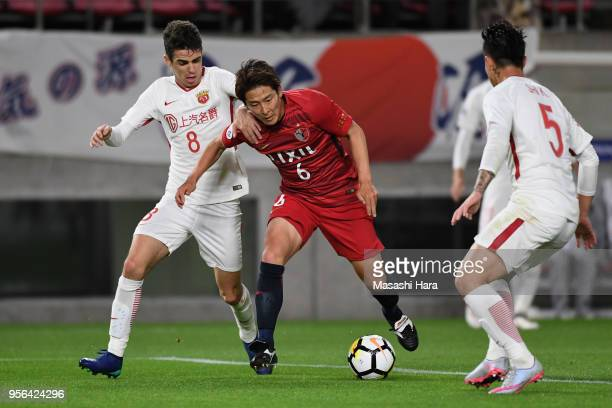 Ryota Nagaki of Kashima Antlers controls the ball under pressure of Oscar and Shi Ke of Shanghai SIPG during the AFC Champions League Round of 16...