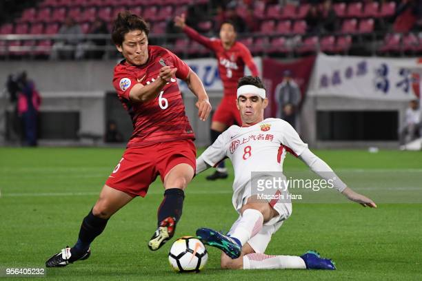 Ryota Nagaki of Kashima Antlers is tackled by Oscar of Shanghai SIPG during the AFC Champions League Round of 16 first leg match between Kashima...