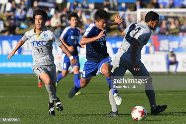 Ryota Nakamura of Azul Claro Numazu competes for the ball against Kenya Okazaki and Mendes of Tochigi SC during the JLeague J3 match between Azul...