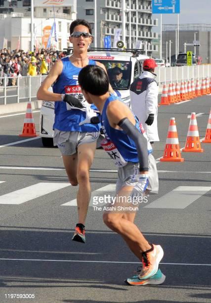 Ryota Natori , 4th runner of Tokai University receives the sash from the 3rd runner Yuichiro Nishikawa on day one of the 96th Hakone Ekiden on...