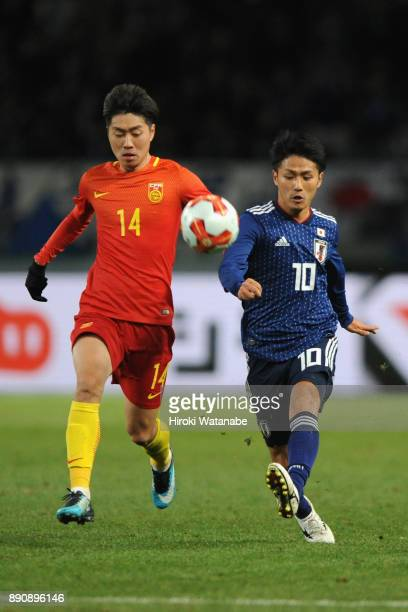 Ryota Oshima of Japan and Fu Huan of China compete for the ball during the EAFF E1 Men's Football Championship between Japan and China at Ajinomoto...