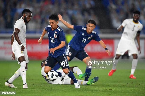 Ryota Oshima of Japan and Joseph Larweh Attamah of Ghana compete for the ball during the international friendly match between Japan and Ghana at...
