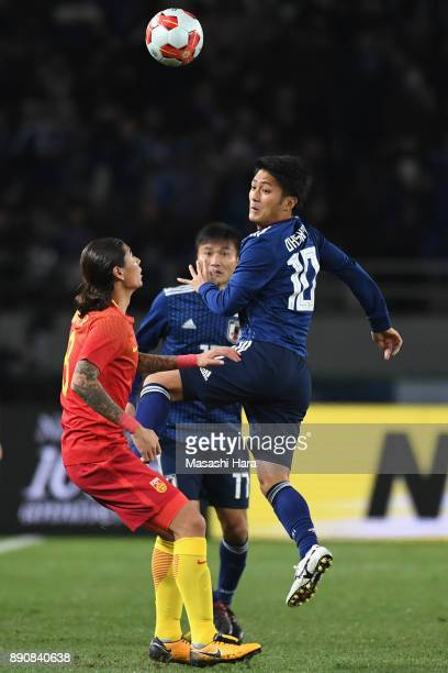 Ryota Oshima of Japan and Zhao Yuhao of China compete for the ball during the EAFF E1 Men's Football Championship between Japan and China at...
