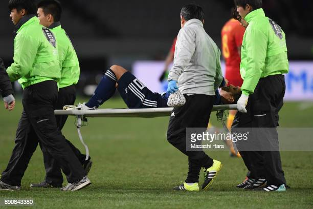 Ryota Oshima of Japan is stretched off during the EAFF E1 Men's Football Championship between Japan and China at Ajinomoto Stadium on December 12...