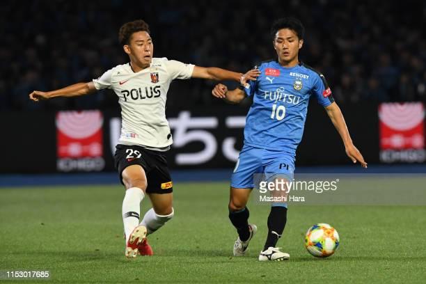 Ryota Oshima of Kawasaki Frontale and Kai Shibato of Urawa Reds compete for the ball during the JLeague J1 match between Kawasaki Frontale and Urawa...
