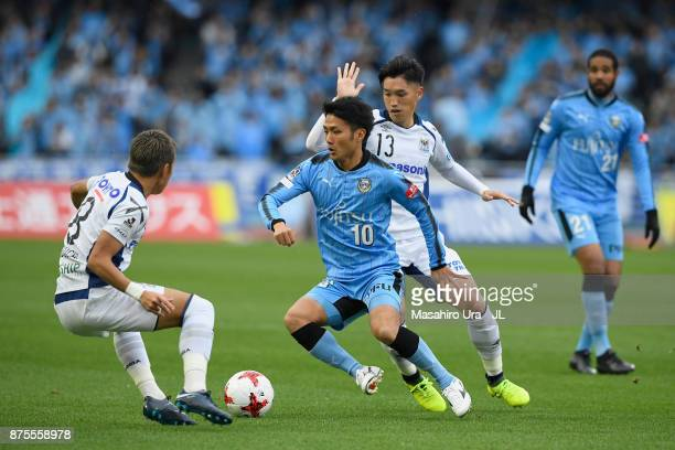 Ryota Oshima of Kawasaki Frontale competes for the ball against Yosuke Ideguchi and Hiroto Goya of Gamba Osaka during the JLeague J1 match between...