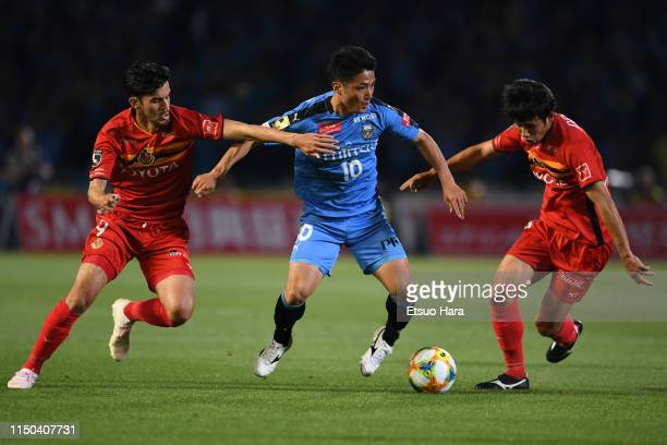 Ryota Oshima of Kawasaki Frontale controls the ball under pressure of Ariajasuru Hasegawa and Takuji Yonemoto of Nagoya Grampus during the JLeague J1...