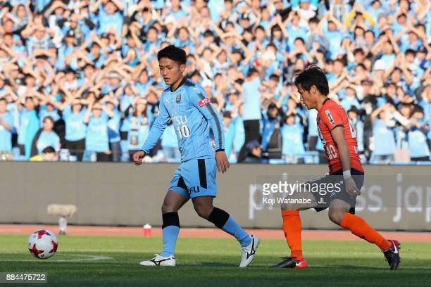 Ryota Oshima of Kawasaki Frontale controls the ball under pressure of Akimi Barada of Omiya Ardija during the JLeague J1 match between Kawasaki...