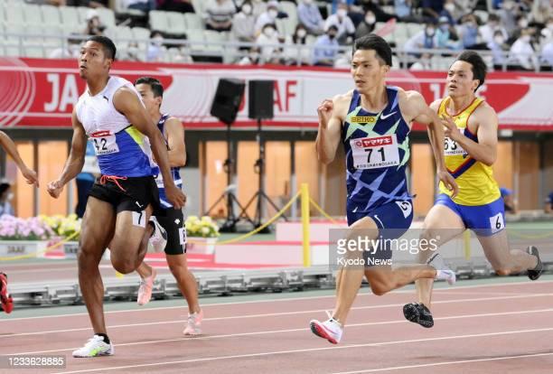 Ryota Yamagata and Abdul Hakim Sani Brown run in the men's 100-meter semifinals at the national athletics championships at Yanmar Stadium Nagai in...