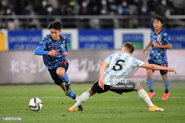 Ryotaro Meshino of Japan takes on Santiago Ascacibar of Argentina during the U-24 international friendly match between Japan and Argentina at the...
