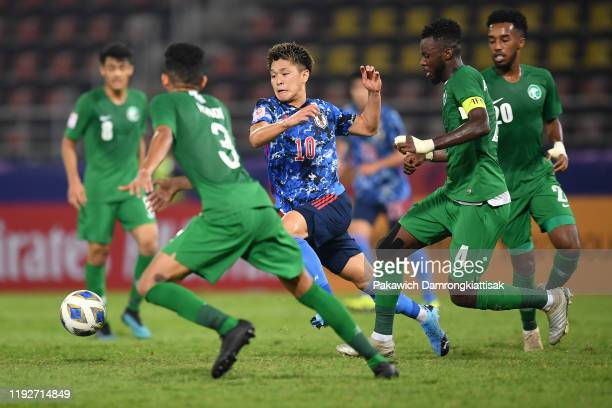 Ryotaro Meshino of Japan takes on Saudi Arabia players during the AFC U-23 Championship match between Japan and Saudi Arabia at Thammasat Stadium on...