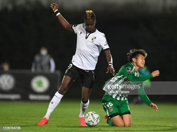 Ryotaro Meshino of Rio Ave competes for the ball with Falaye Sacko of Vitoria Guimaraes SC during the Liga NOS match between Rio Ave FC and Vitoria...