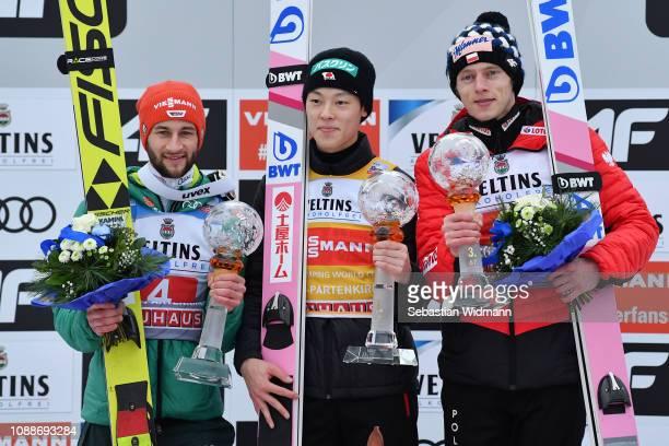 Ryoyu Kobayashi of Japan celebrates his first place with second placed Markus Eisenbichler of Germany and Dawid Kubacki of Poland on day 4 of the...