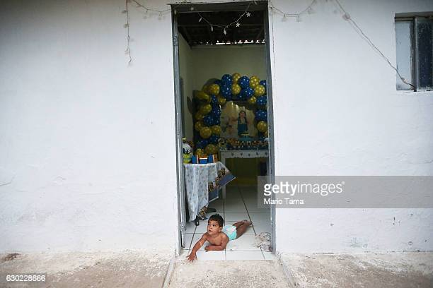 Ryquelme Kauan who was born with microcephaly attempts to crawl outside toward his mother Avila as she cleans before the start of his one year...