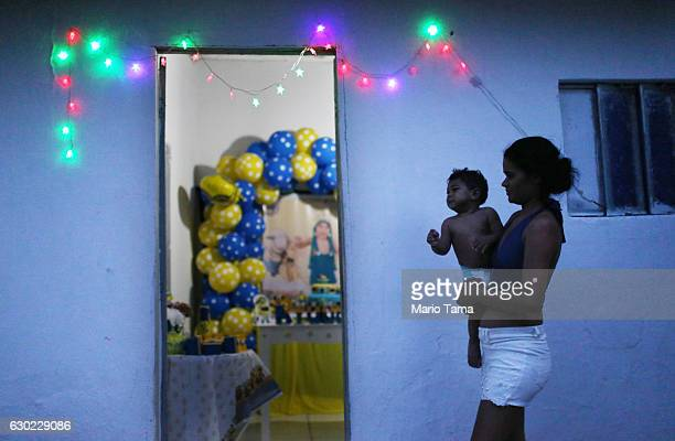 Ryquelme Kauan who was born with microcephaly is carried by his mother Avila before the start of his one year birthday party at their house on...