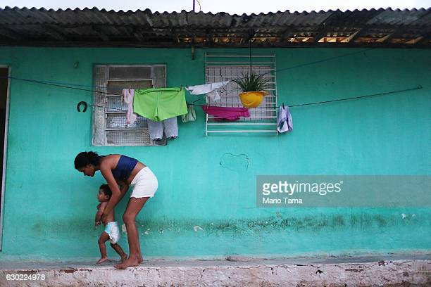 Ryquelme Kauan who was born with microcephaly is held by his mother Avila as she attempts to teach him to walk before the start of his one year...