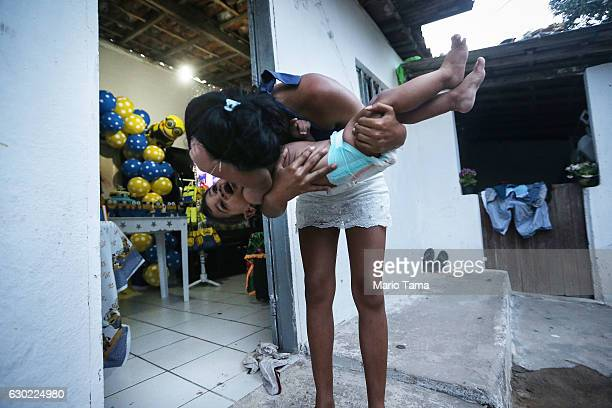 Ryquelme Kauan who was born with microcephaly is held by his mother Avila before the start of his one year birthday party at their house decorated...