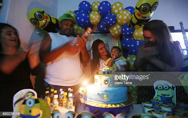 Ryquelme Kauan who was born with microcephaly is held by his mother Avila as stepfather Marcelo stands by at his one year birthday party on December...